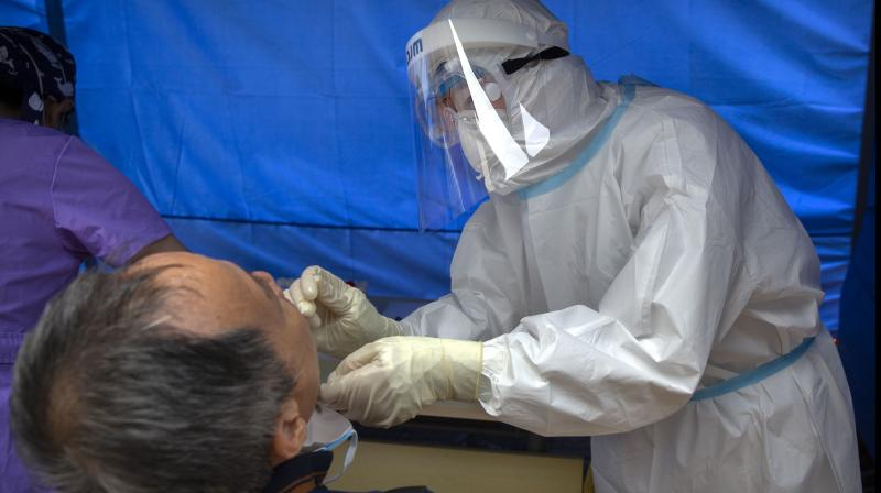 A worker wearing a protective suit swabs a man's throat for a coronavirus test at a community health clinic. AP
