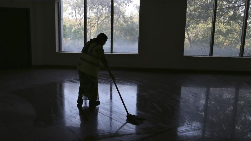 A municipal worker cleans the floor of a room to be used as an isolation ward for coronavirus asymptomatic people at an athletic stadium in Hyderabad, March 17, 2020. (AP)