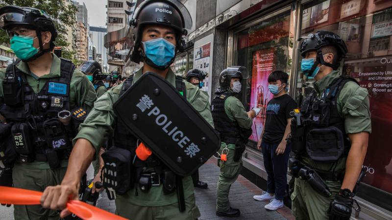 Police question a man as they patrol the area after protesters called for a rally in Hong Kong on September 6, 2020 to protest against the government's decision to postpone the legislative council election due to the COVID-19 coronavirus, and the national security law. (AFP)