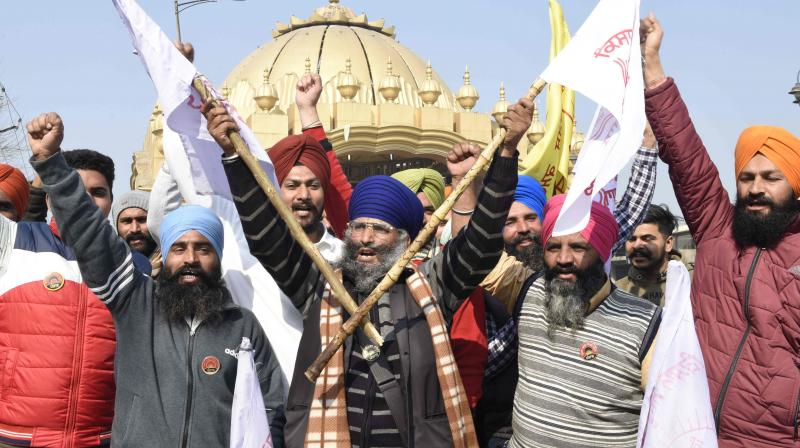 Farmers shout slogans blocking a highway during a roadblock-protest, part of their continuing demonstration against the central government's recent agricultural reforms, on the outskirts of Amritsar on February 6, 2021. (AFP)