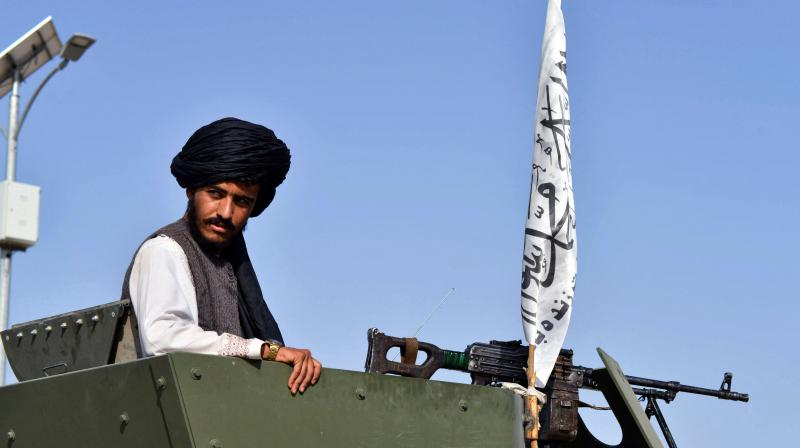 A Taliban fighter stands on an armoured vehicle with a Taliban flag during a parade along a road to celebrate after the US pulled all its troops out of Afghanistan, in Kandahar on September 1, 2021 following the Taliban's military takeover of the country. (Photo:AFP)