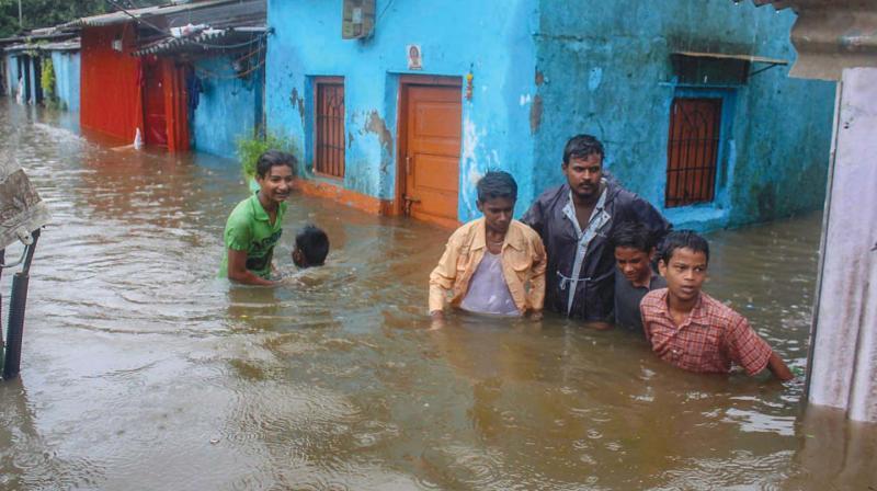 People make their way through a water-logged street after heavy rains, in Kalyan, Mumbai on Saturday. (Photo: PTI )