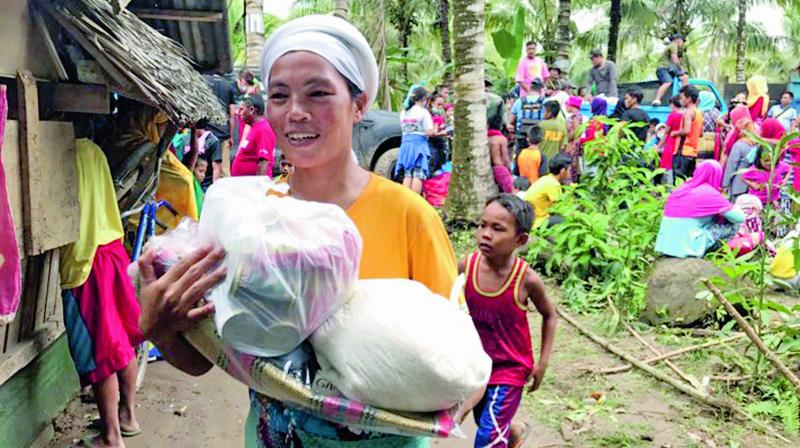 A resident smiles as she walks home with relief supplies being distributed to storm-affected villages of Lanao del Norte on Sunday in southern Philippines. (Photo: AP)
