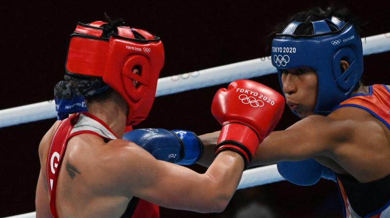 Germany's Nadine Apetz (red) and India's Lovlina Borgohain fight during their women's welter (64-69kg) preliminaries round of 16 boxing match during the Tokyo 2020 Olympic Games at the Kokugikan Arena in Tokyo. (Photo: AFP)