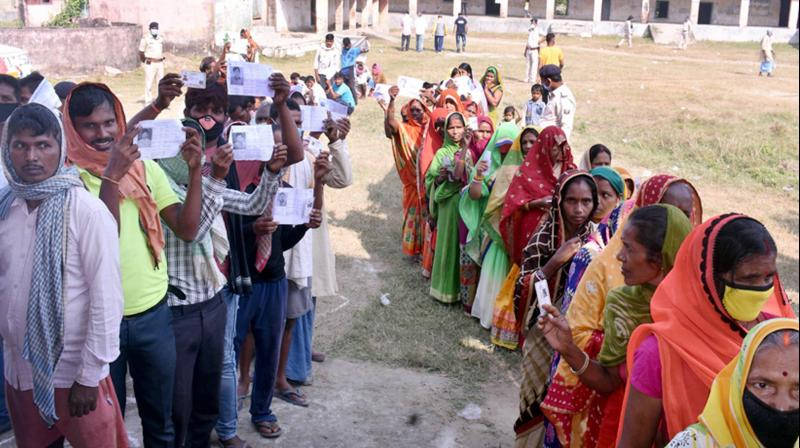 Voters stand in a queue at a polling station to cast their votes during the first phase Bihar assembly polls, amid the ongoing coronavirus pandemic, at Ara constituency in Bhojpur district, Wednesday, Oct. 28, 2020. (PTI Photo)
