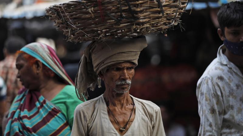 A man walks balancing a basket on his head at a vegetable market in Lucknow, India. (AP)