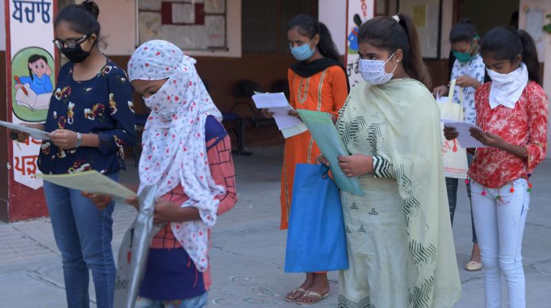 Students wearing facemasks as a preventive measure against the Covid-19 coronavirus wait to submit their national scholarship portal registration forms at a Government Girls School in Amritsar on October 15, 2020. (AFP)