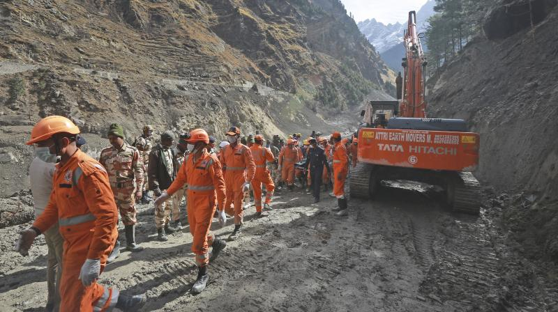 National Disaster Response Force (NDRF) personnel clear debris after a portion of the Nanda Devi glacier snapped off, releasing water trapped behind it in Tapovan, Uttarakhand on Tuesday, February 9, 2021. (AP Photo)