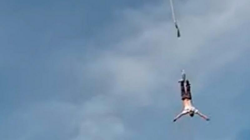 In the video, a group of people are seen looking as a crane hoists the man above ground. Moments later, the jump begins.Within few seconds, the rope snaps and man was seen plummeting down on the safely cushion placed below. (Screengrab)