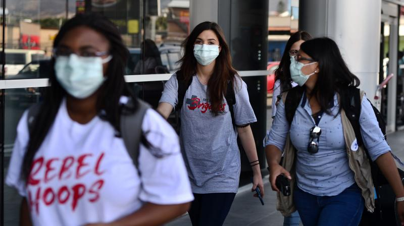 Passengers wear protective face masks to prevent the spread of the new Coronavirus, COVID-19. AFP Photo