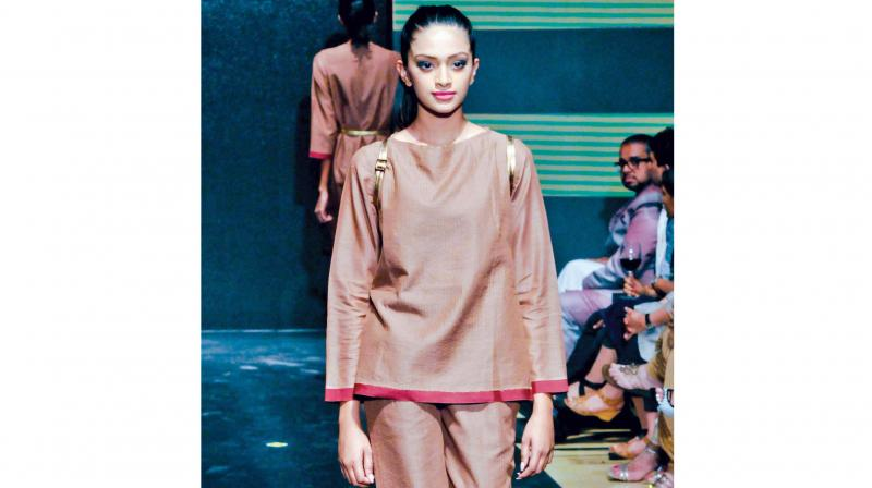 This model is wearing a brown outfit that is colour blocked with a bright magenta.