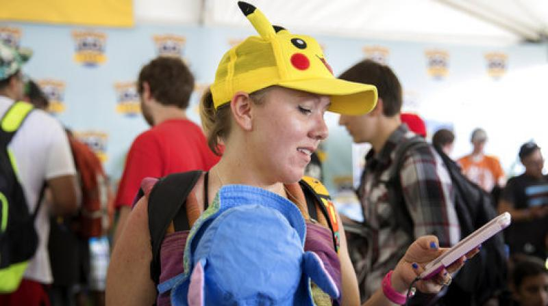 Lauren Schuster of Miami looks at her phone as she struggles to get her Pokemon Go game to quit crashing at the Pokemon Go Fest Saturday, July 22, 2017, at Grant Park in Chicago. (Photo: AP)