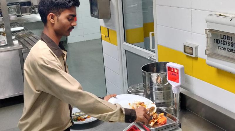 A resort worker weighs food wasted by a guest. Leftovers are charged Rs 100 per 10 grams.