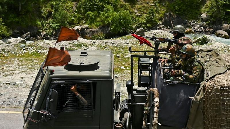 Indian army soldiers ride in a convoy along a highway leading towards Leh, bordering China, in Gagangir on 17 June 2020. (AFP)