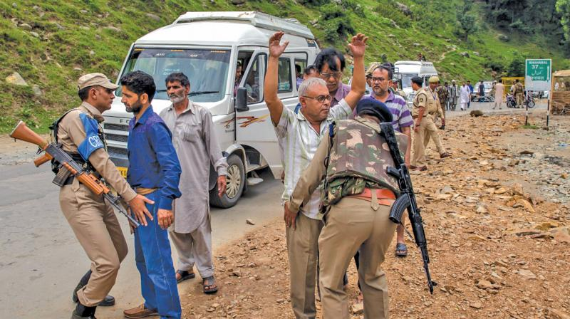 Paramilitary jawans frisk a Kashmiri civilian (left) and a pilgrim (right) as others wait for their turn at a temporary checkpoint near the base camp in Pahalgam. (Photo: AP)