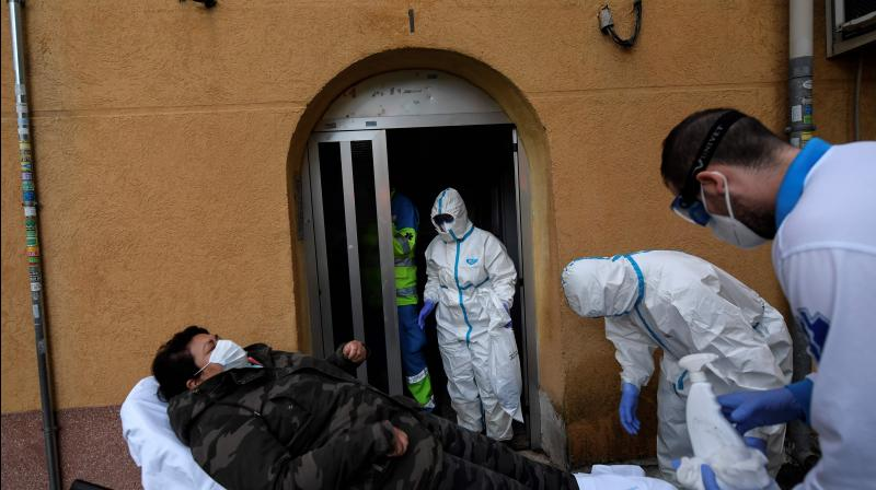 Healthcare workers of the Medical Emergency Services of Madrid (SUMMA 112) UVI-6 unit, transfer a suspected COVID-19 patient on a stretcher from her home to a hospital in Madrid. AFP Photo