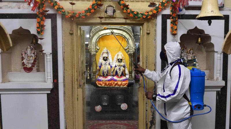 An employee, wearing a PPE kit, sanitizes the premises of Vithal Rukmini temple, in Mumbai, Sunday, Nov 15, 2020. (PTI)