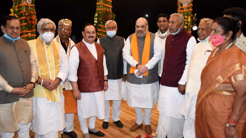Patna: Union Home Minister Amit Shah and BJP National President JP Nadda, Bihar Governor Phagu Chauhan, HAM (S) chief Jitan Ram Manjhi with Bihar Chief Minister Nitish Kumar, Deputy Chief Ministers Renu Devi and Tarkishore Prasad pose for a group photograph after the oath-taking ceremony at Raj Bhawan in Patna, Monday, Nov. 16, 2020. (PTI Photo)