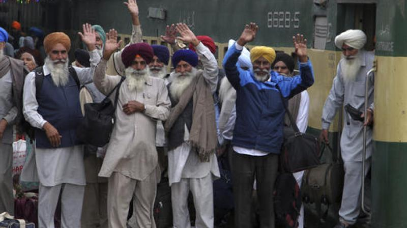 Indian Sikh pilgrims waves upon their arrival at Wagah railway station near Lahore. (Photo: AP)
