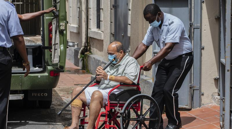 Antigua and Barbuda businessman Mehul Choksi is taken to a police van via a wheelchair by a police officer after attending a court hearing, in Roseau, Dominica. (AP)