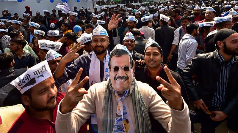 An Aam Aadmi Party worker, dressed as party chief Arvind Kejriwal, celebrates along with others the party's success in the Delhi Assembly polls, at party headquarters in New Delhi, Tuesday, Feb. 11, 2020. (PTI Photo)