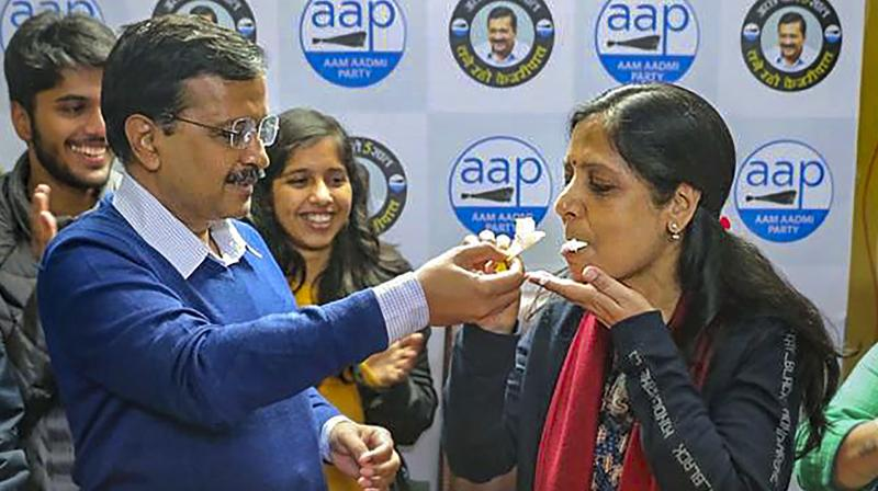 Aam Aadmi convenor Arvind Kejriwal with wife Sunita (right) and party leader Raghav Chadha (centre) address supporters after the party's victory in the Delhi Assembly polls, at the AAP office in New Delhi, Tuesday, Feb. 11, 2020. (PTI Photo)