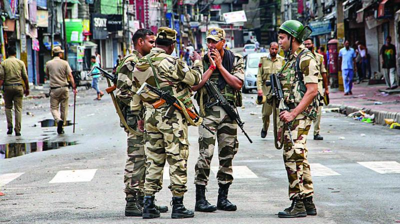 Security personnel stand guard during restrictions in Jammu on Monday. Restrictions and night curfews were imposed in several districts of Jammu and Kashmir as the Valley remained on edge with the authorities stepping up security deployment. (Photo: PTI)