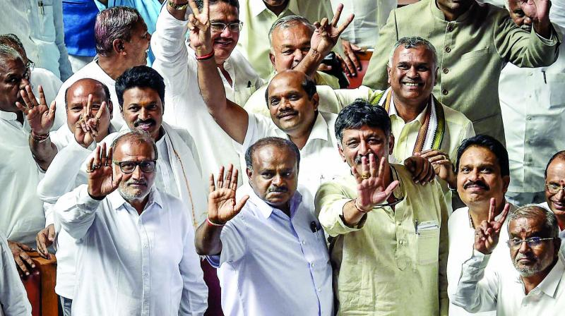 Karnataka CM H.D. Kumaraswamy, with other JD(S) and Congress leaders, waves to the media after his coalition government won the trust vote by voice vote at Vidhana Soudha in Bengaluru. (Photo: PTI)