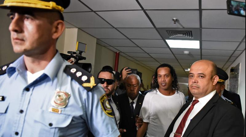 Brazilian retired footballer Ronaldinho (second right) arrives at Asuncions Justice Palace on Friday to testify about his irregular entry into the country. AFP Photo