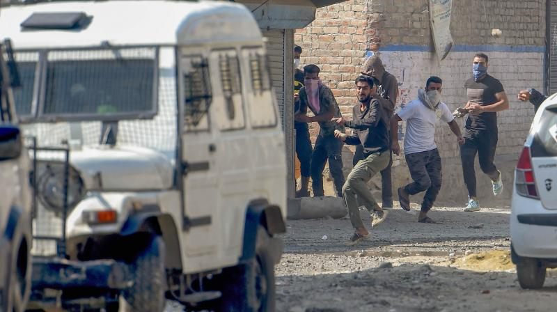 : Protesters throw stones on security personnel after an encounter with militants, at Batamaloo in Srinagar. PTI Photo
