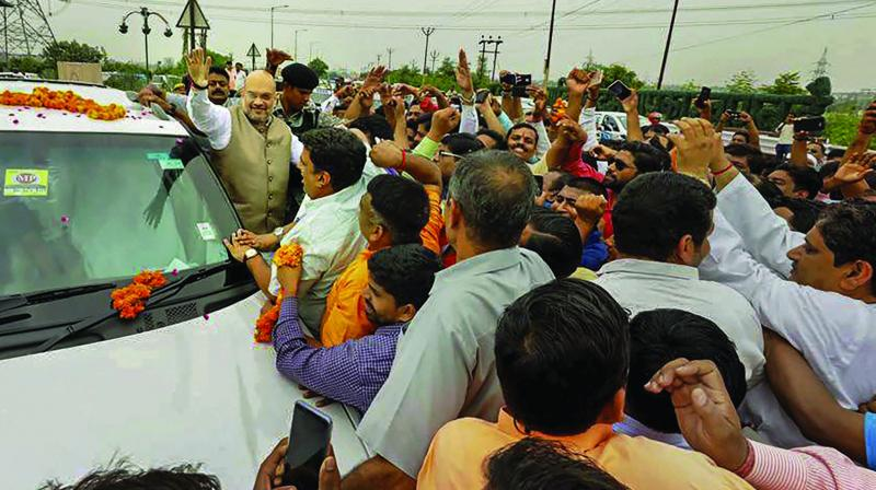 BJP president Amit Shah is greeted by party workers at Rajnagar Extension in Ghaziabad on Sunday while he was on his way to Meerut to attend the BJP's state working committee meeting. (Photo: PTI)