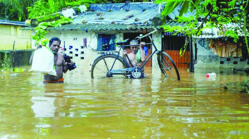 Villagers wade through flood waters at Bhoisahi in Bhubaneswar.