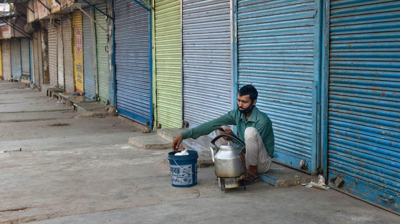 A man sits outside the closed shops at Khari Baoli Road during the nationwide lockdown, imposed in wake of the coronavirus pandemic, in New Delhi. PTI photo