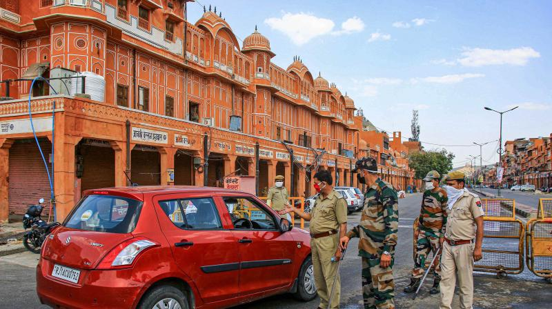Security personnel stop commuters at Ramganj Bazar in Jaipur. PTI photo