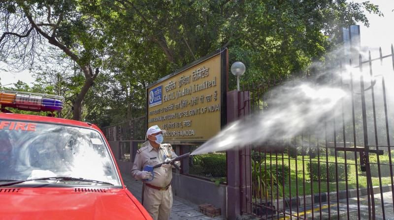 Fire personnel spray disinfectant on the entry gates at Film City, in the wake of coronavirus pandemic, during the nationwide lockdown in Noida. PTI photo