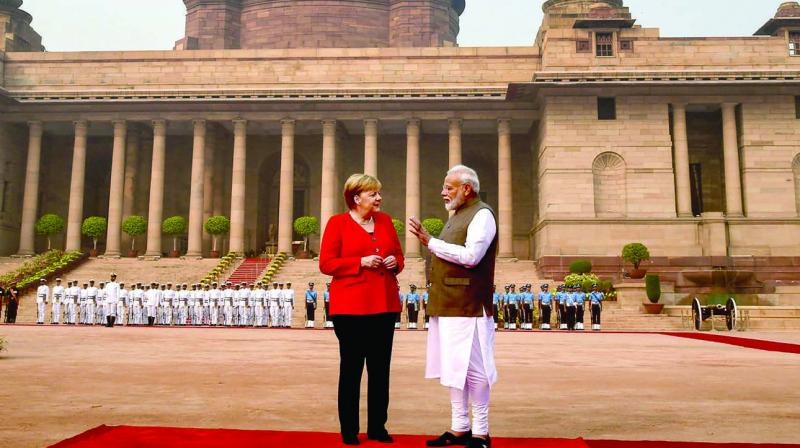 Prime Minister Narendra Modi interacts with German Chancellor Angela Merkel during her ceremonial reception at Rashtrapati Bhavan in New Delhi on Friday. (Photo: PTI)
