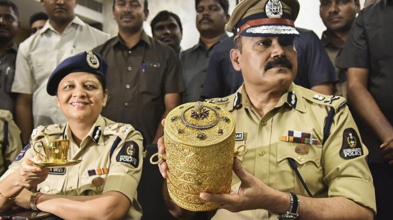 Hyderabad Police Commissioner Anjani Kumar along with a senior police officer shows to media the three-tier golden tiffin box and a golden cup after their recovery. (Photo: PTI)