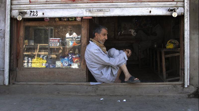 A Kashmiri shopkeeper sits at the entrance of his half closed shop during lockdown in Srinagar. AFP Photo