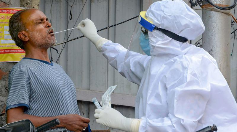 A health worker collects swab samples of a man for COVID-19 testing in a containment zone amid lockdown in Guwahati. PTI