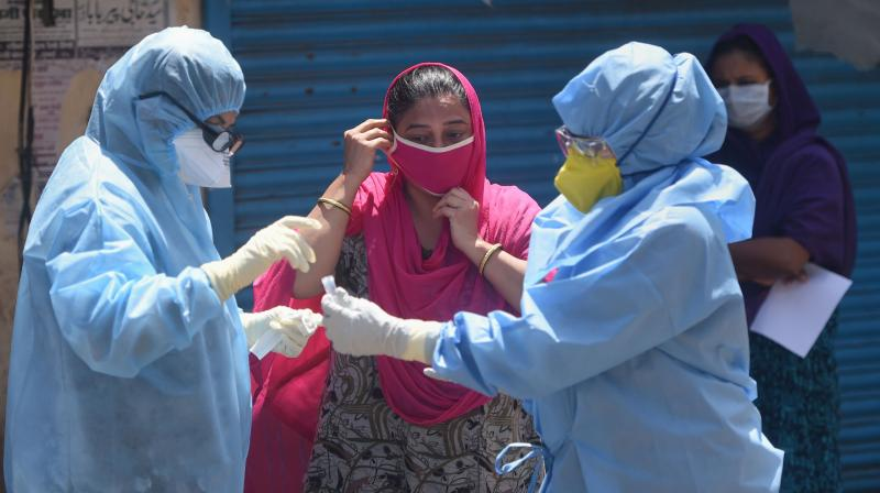 Doctors wearing protective suits examine a woman in a bid to detect COVID-19 positive cases, at a camp at Sewri slums during the nationwide lockdown, in Mumbai. PTI Photo