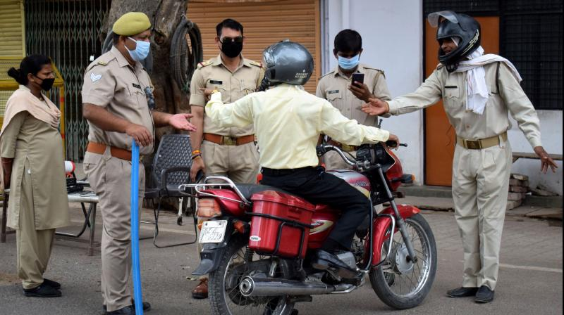 Police personnel issue challan to a commuter for allegedly violating the COVID-19 lockdown, in Prayagraj, UP. PTI Photo
