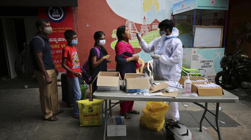 A health worker in protective suit collects swab sample of a traveler to test for COVID-19 outside a train station in Bengaluru, India, June 16, 2021. (AP /Aijaz Rahi)