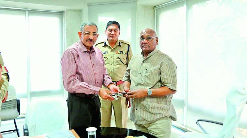 Retired IPS officer C Anjaneya Reddy handing over the weapon to TSPA Director Santosh Mehra.