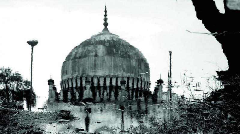 Reflection of one of the Qutb Shahi tombs post rains in a puddle of muddy rain water