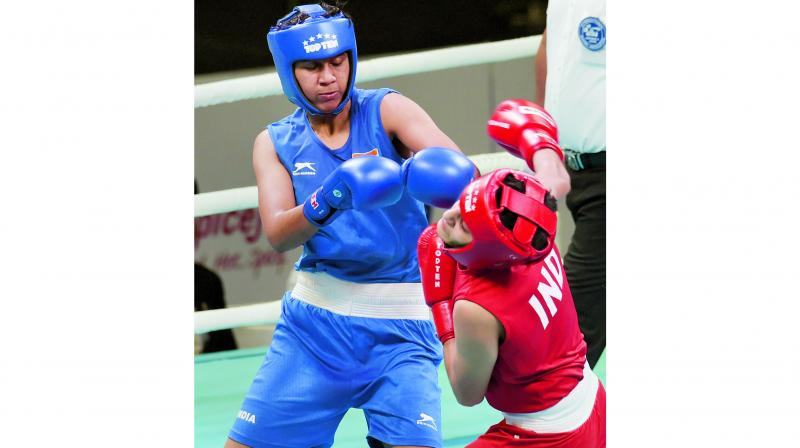 Shashi Chopra (left) lands a punch on Sonia in their women's featherweight 57kg category semi-final of the India Open boxing tournament in New Delhi on Wednesday. (Photo: PTI)