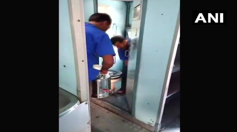 In the video, which was circulated on social media, in the past few days, a vendor was seen coming out of a train toilet with tea and coffee cans, indicating that water was being mixed in the cans inside the toilet. (Photo: ANI/Twitter)