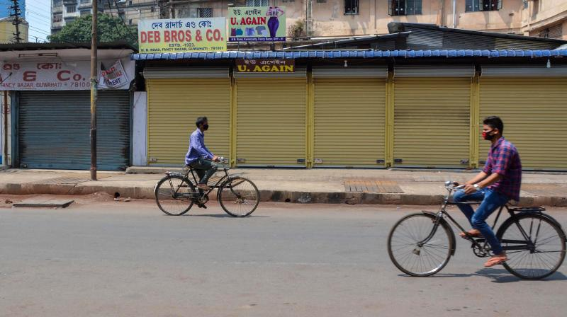 Stray cyclists seen on the Fancy Bazaar road in Guwahati during the 'Vyapar Bandh' called by the Assam Chamber of Commerce on March 23, 2020. The Assam government has extended the shutdown until March 31. (PTI)