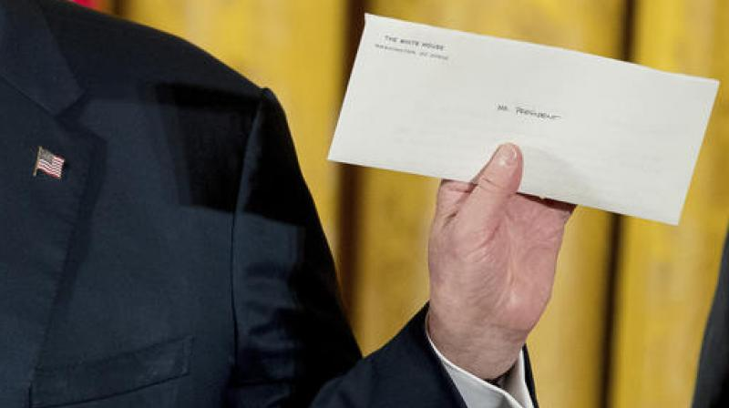 President Donald Trump holds up a letter left for him by former President Barack Obama as he speaks at a White House senior staff swearing in ceremony in the East Room of the White House. (Photo: AP)