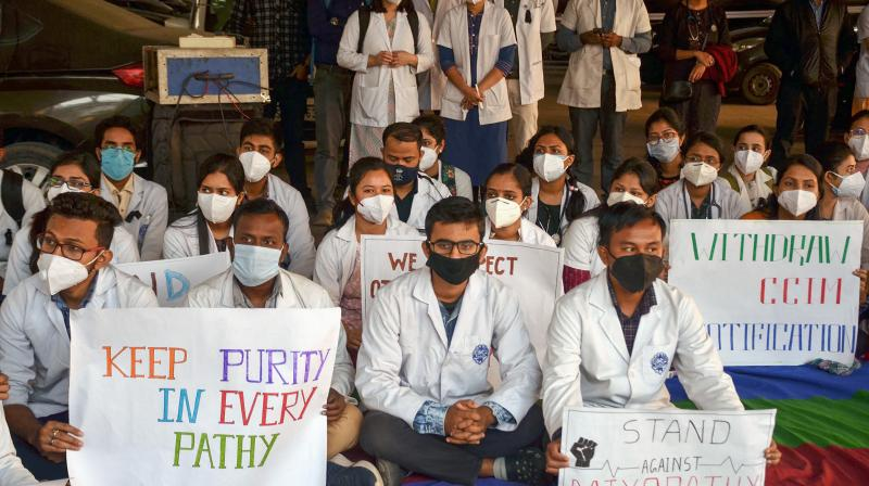 Members of Junior doctors' Association stage a protest in solidarity with Indian Medical Association's strike against Mixopathy and demanding the withdrawal of CCIM notification, at Guwahati Medical College and Hospital (GMCH) in Guwahati, Friday, Dec. 11, 2020. In the notification, Centre has allowed Post Graduate (PG) students of Ayurveda to perform a variety of general surgery including orthopedic, ophthalmology, ENT and dental procedures. (PTI)