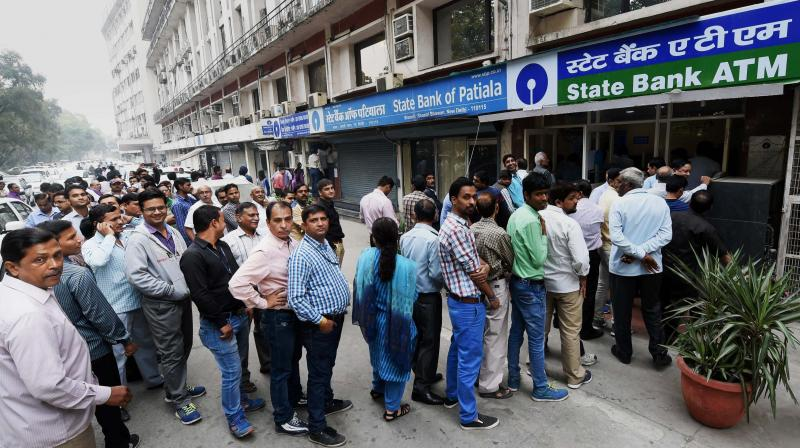 People queue up outside an ATM to withdraw money at Shastri Bhavan in New Delhi. (Photo: PTI)